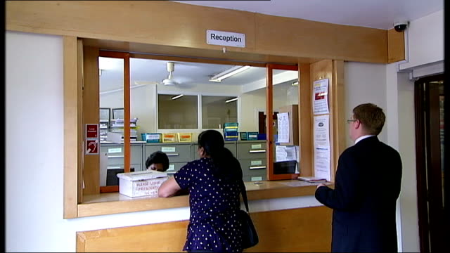 honeypot medical centre ext entrance to doctors' surgery at honeypot medical centre close shots of swine flu notice in window receptionist talking on... - symptom stock videos and b-roll footage