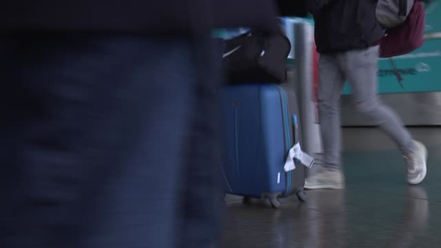 essex stansted airport ext passengers arriving at airport with wheely suitcases and other luggage / various of people with wheely bags along /... - ライアンエアー点の映像素材/bロール