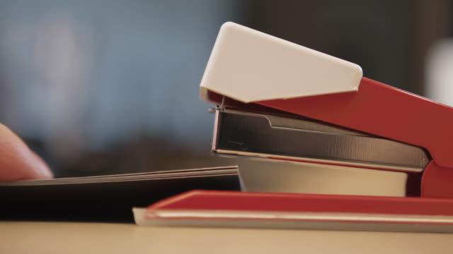 stapler on desk, stapling documents, close up 3 - ホッチキス点の映像素材/bロール