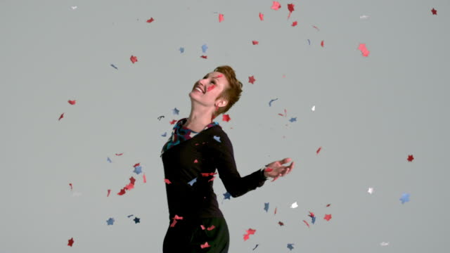 Star confetti slowly floating around woman happily looking up