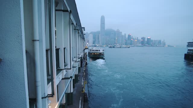 stockvideo's en b-roll-footage met star ferry boat leaving a wake on the water in kowloon pier in victoria harbour hong kong. - wide shot - star ferry