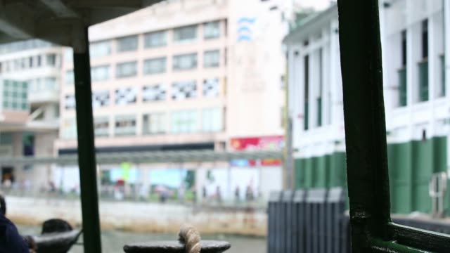 stockvideo's en b-roll-footage met a star ferry co vessel owned by wharf holdings ltd moored at the pier in the tsim sha tsui district of kowlooon in hong kong an employee prepares a... - star ferry
