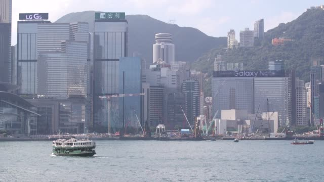 A Star Ferry Co vessel owned by Wharf Holdings Ltd sail across Victoria Harbor past commercial and residential buildings in Hong Kong China on Monday...
