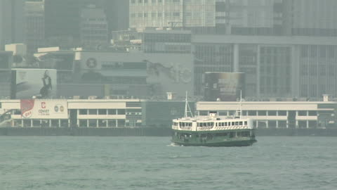 ws star ferry crossing victoria harbor on foggy day, downtown buildings in background / hong kong, china - star ferry stock-videos und b-roll-filmmaterial