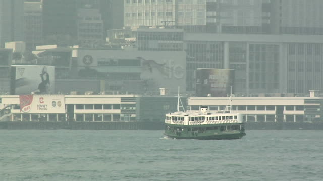stockvideo's en b-roll-footage met ws star ferry crossing victoria harbor on foggy day, downtown buildings in background / hong kong, china - star ferry