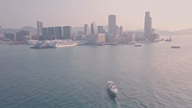 stockvideo's en b-roll-footage met star ferry from hong kong island to kowloon at sunrise. aerial drone view - star ferry