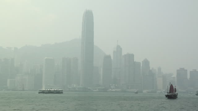 WS Star Ferry on foggy day in Victoria Harbor, downtown buildings with International Finance Centre in background / Hong Kong, China