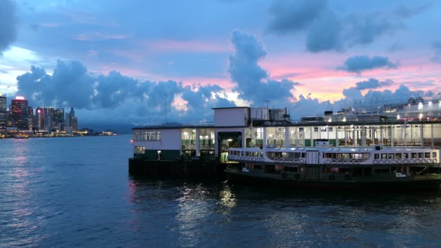 stockvideo's en b-roll-footage met star ferry sailing across victoria harbour between tsim sha tsui and hong kong island, with the iconic hong kong city skyline in the background at twilight - star ferry
