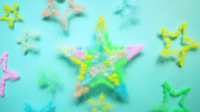 star shapes made with multi colored glitter powder exploding towards camera and becoming defocused on green background, glittering bokeh - multi coloured stock videos & royalty-free footage