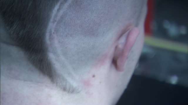 Star shaved in to Mohawk haircut w/ lines on the side of unidentifiable Caucasian man's head as he sits in barber's chair getting hair swept from...