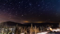 Star Time-lapse: Stars Moving Above Small House In The Mountains In Winter. Ukraine, Carpathian