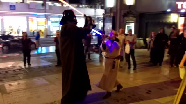 star wars characters fighting with light sabers outside the tcl chinese theater in hollywood the 12day line for the new star wars film premiere is... - tcl chinese theater stock-videos und b-roll-filmmaterial