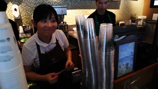 vídeos de stock, filmes e b-roll de starbucks barista in china takes customer's order - starbucks