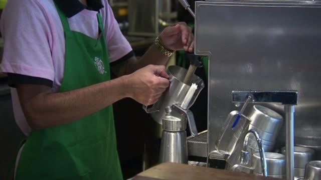 vídeos de stock, filmes e b-roll de starbucks coffee company barista behind counter no face - starbucks