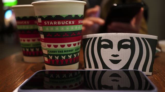 starbucks coffee cup especially made for christmas on the table. - coffee cup stock videos & royalty-free footage