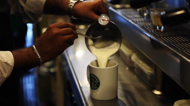 vídeos de stock, filmes e b-roll de starbucks employee prepares beverage in kuala lumpur - starbucks