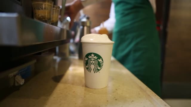 vídeos de stock, filmes e b-roll de starbucks location in mexico city mexico on february 17 wide shot shot of a starbucks employee pouring a latte into a stabucks cup on the counter... - starbucks