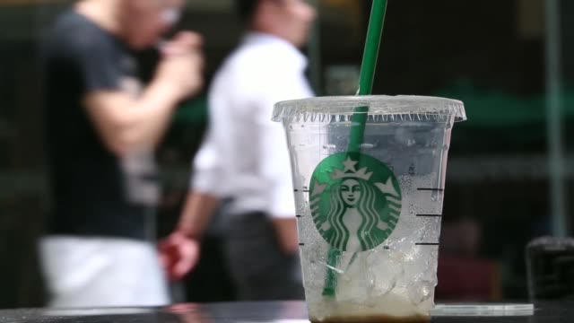 a starbucks logo is displayed on a plastic cup of frozen coffee at a starbucks corp store in the luohu district of shenzhen china on monday aug 4... - awning stock videos and b-roll footage