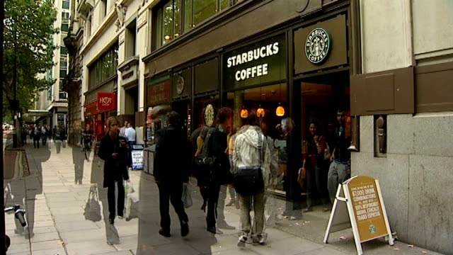 Starbucks plays down row following comment on British economy TX People along on street past branch of Starbucks Coffee cafe