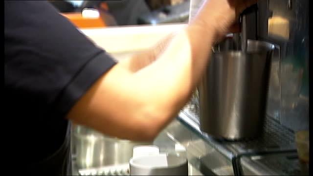 Starbucks plays down row following comment on British economy R12080803 London Starbucks staff member making latte coffee Customers drinking coffee...
