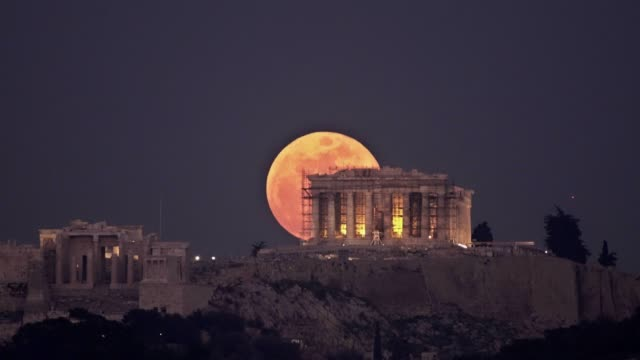 stargazers in athens had the chance to witness a rare super blue blood moon rising behind the parthenon temple on the acropolis of athens tonight the... - acropolis athens stock videos & royalty-free footage