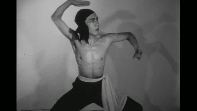 1948 staring intensely into camera, man (chao-li chi) executes kung fu blocking sequences in an empty room - カンフー点の映像素材/bロール