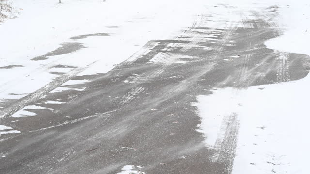 stark wind blowing podwer snow across the asphalt surface of road.  you can see the tracks that a vehicle has left in the snow. bandenburg. germany - slippery stock videos & royalty-free footage