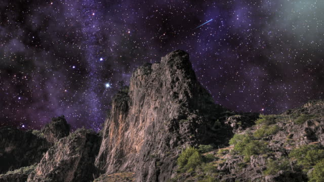 starry heavens turn above a granite sheer-faced peak. - digital enhancement stock videos and b-roll footage