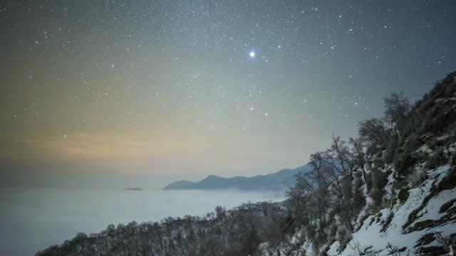 starry night and roaring sea of clouds on a snow mountain - 不在点の映像素材/bロール