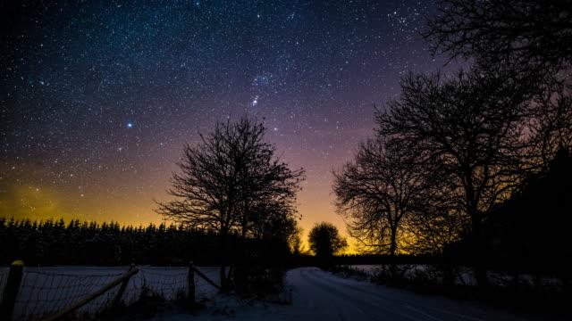 TIMELAPSE:  Starry night sky above rural winter landscape - 4K Nature/Wildlife/Weather