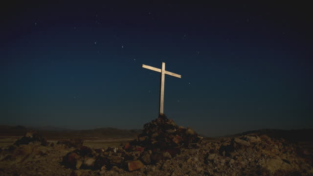 vidéos et rushes de t/l la ws starry night to dawn with wooden cross atop rocks in barren landscape / tecopa, california, usa - croix religieuse