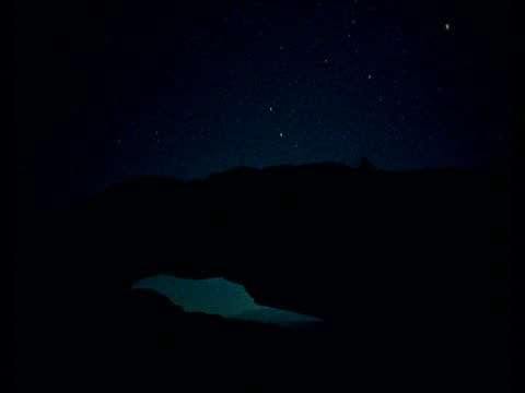 stars and moon track across sky behind rock arch, utah - natural arch stock videos & royalty-free footage