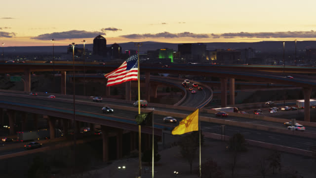 stars and stripes and new mexico flag flying in front of albuquerque skyline and freeways at sunset - ascending drone shot - new mexico stock videos & royalty-free footage