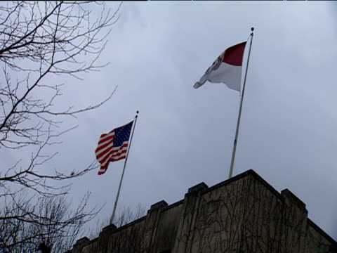 Stars and Stripes flying on roof of building next to flag of Cornell University New York State
