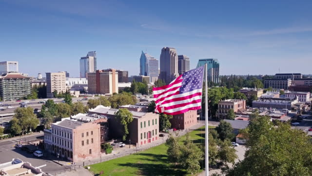Stars and Stripes Flying Over Old Town Sacramento - Aerial Shot