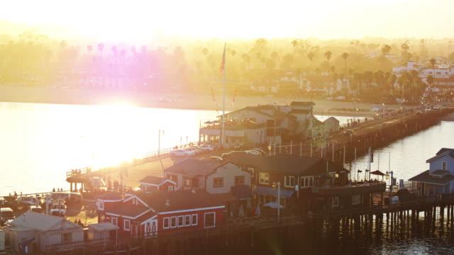 vídeos de stock e filmes b-roll de stars and stripes flying over stearns wharf, santa barbara at sunset - aerial shot - santa barbara