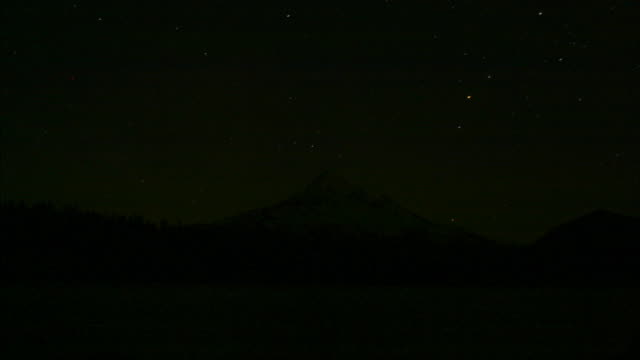 stars and the moon move across the sky over mt. hood and hidden lake in oregon. - mt hood stock videos & royalty-free footage