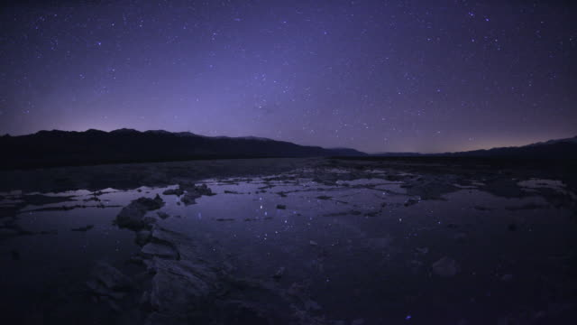 ws t/l   stars at night reflecting  in water of sea  / badwater, death valley national park, california, usa - death valley national park stock videos & royalty-free footage
