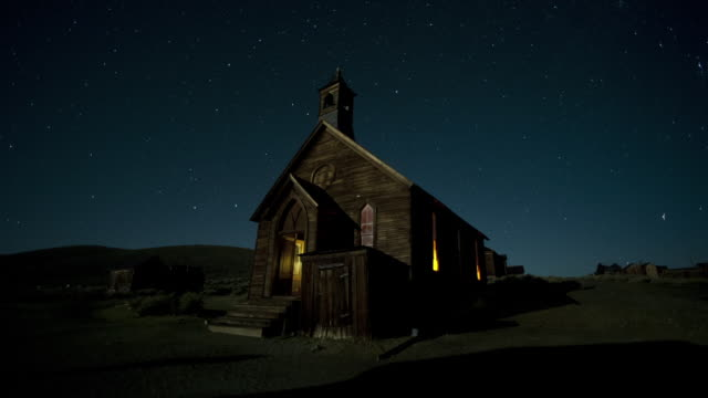 stars glow above a church from the 1880s in bodie ghost town, california. - california gold rush stock videos and b-roll footage