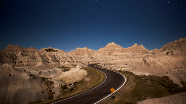 stars move by in a night sky over a badlands national park highway. - badlands national park video stock e b–roll