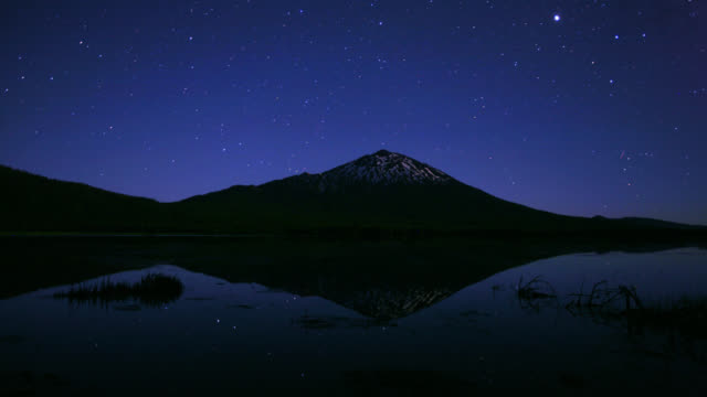 time lapse wide shot stars move in darkening sky over mount bachelor and sparks lake in oregon - inarcare la schiena video stock e b–roll