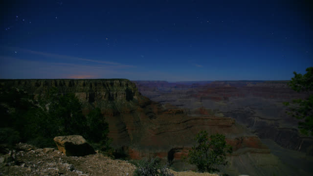 time lapse high angle long wide shot stars move over south rim of grand canyon night to day, arizona - 時点の映像素材/bロール