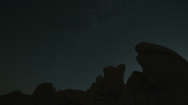 t/l ws pan stars moving across night sky above white tank rock formations in joshua tree national park / california, usa - joshua tree national park stock videos & royalty-free footage
