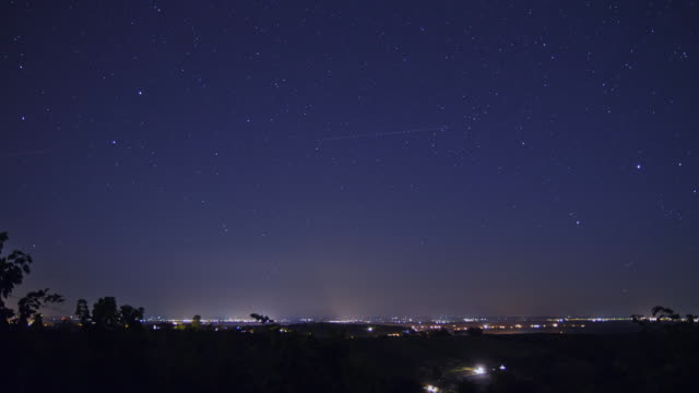 hd time-lapse: stars over night cityscape - star trail stock videos & royalty-free footage