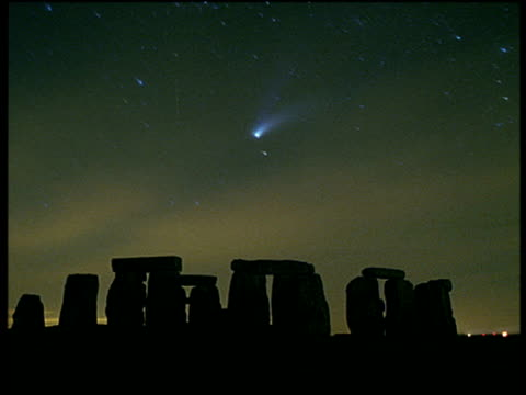 stars spin with comet and streaks of sunset laced clouds pass over silhouetted stonehenge wiltshire - stonehenge stock videos and b-roll footage