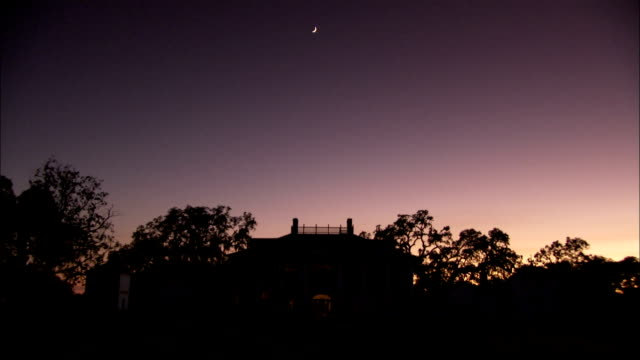 Stars start to appear in the sky above a plantation house. Available in HD.