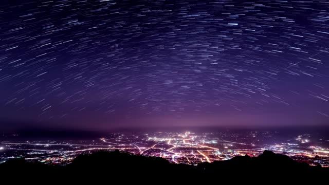 sterne wanderwege in klaren himmel und beleuchtete stadt, zeitraffer. - sternenspur stock-videos und b-roll-filmmaterial