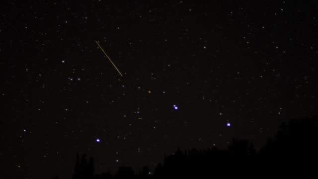 stars wheel in night sky as aircraft streak across. - stern weltall stock-videos und b-roll-filmmaterial