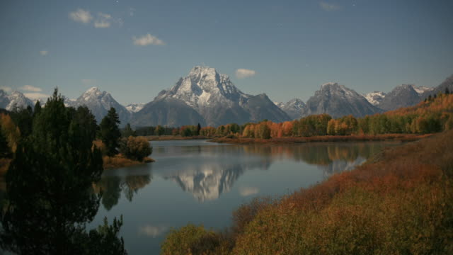 stars wheel over mountains, trees with autumnal colours in foreground. - mt moran stock videos & royalty-free footage