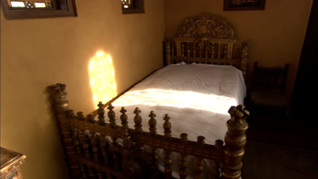 a star-shaped lamp hangs from the ceiling of a bedroom in hearst castle. - bedroom stock videos & royalty-free footage